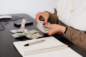woman counting money with planner on desk